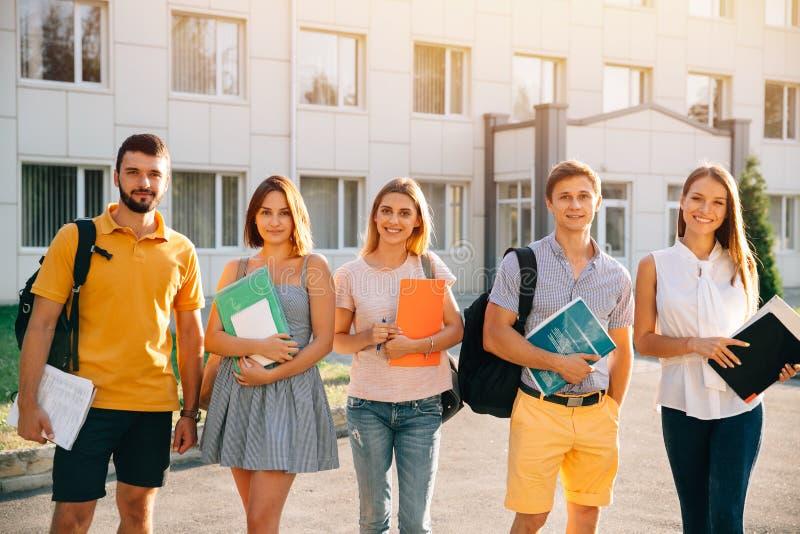 小组偶然成套装备的愉快的学生有书的,当站立在大学时背景  库存图片
