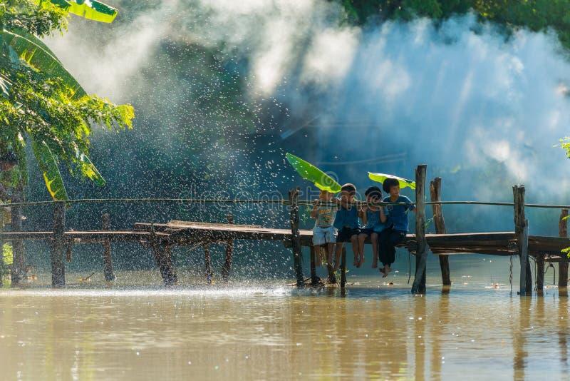 小组农村孩子一起坐木桥 免版税图库摄影