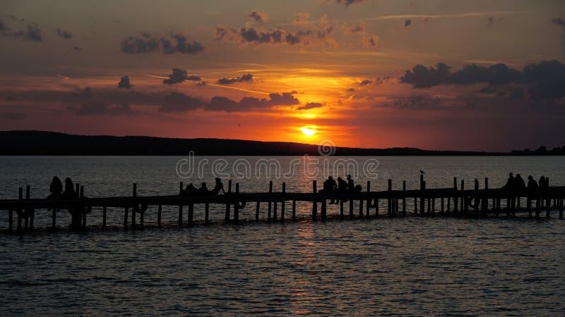 小组剪影观看的日落日落的无法认出的人 图库摄影