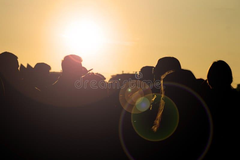 小组剪影走在城市的朋友在日落期间反对天空 免版税库存图片