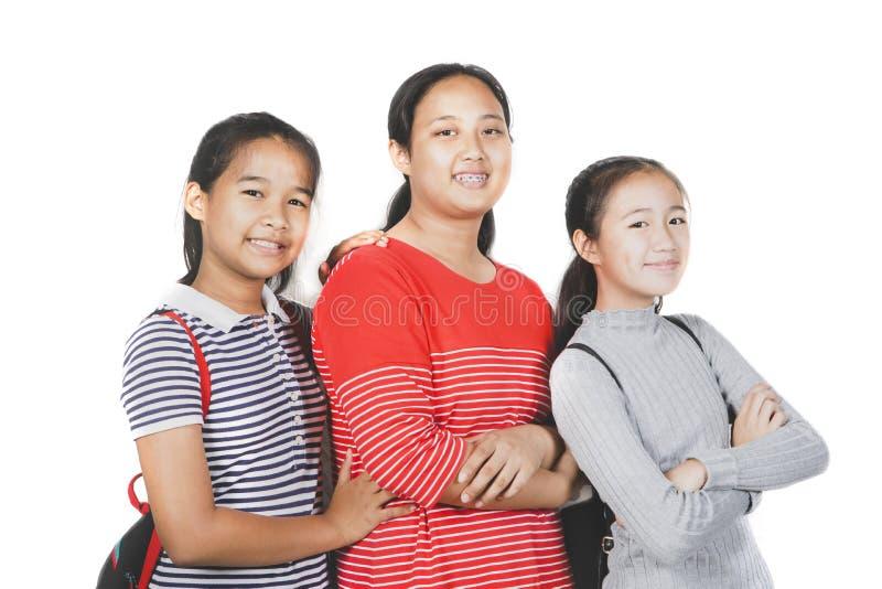 小组反对白色背景的亚洲少年笑容身分 免版税库存照片