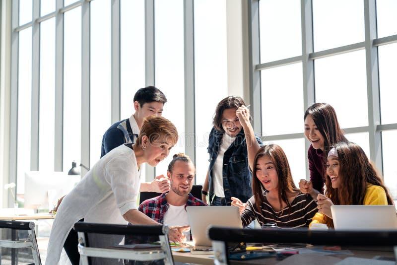 小组变化人合作微笑和激发在成功与膝上型计算机一起使用在现代办公室 免版税库存照片