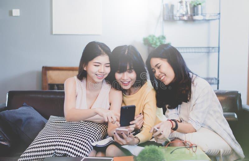 小组咖啡店的年轻亚裔女性朋友,使用数字式设备,聊天与智能手机 库存照片