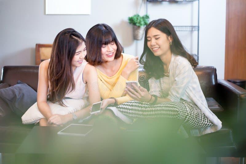 小组咖啡店的年轻亚裔女性朋友,使用数字式设备,聊天与智能手机 免版税库存照片