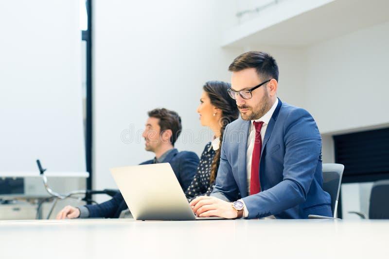 小组商人在一次会议在办公室,工作在计算机上 库存图片
