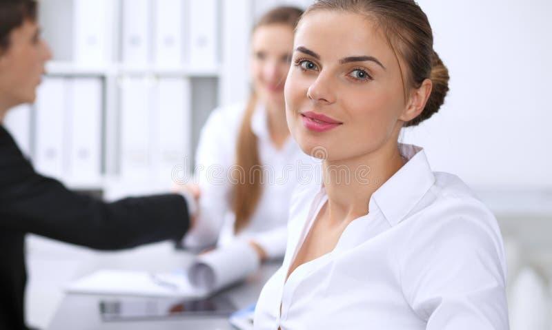 小组商人在关于办公室背景的会议上  在一名美丽的深色的妇女的焦点 库存照片