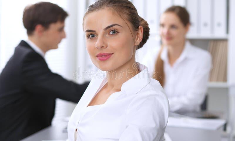 小组商人在关于办公室背景的会议上  在一名美丽的深色的妇女的焦点 图库摄影