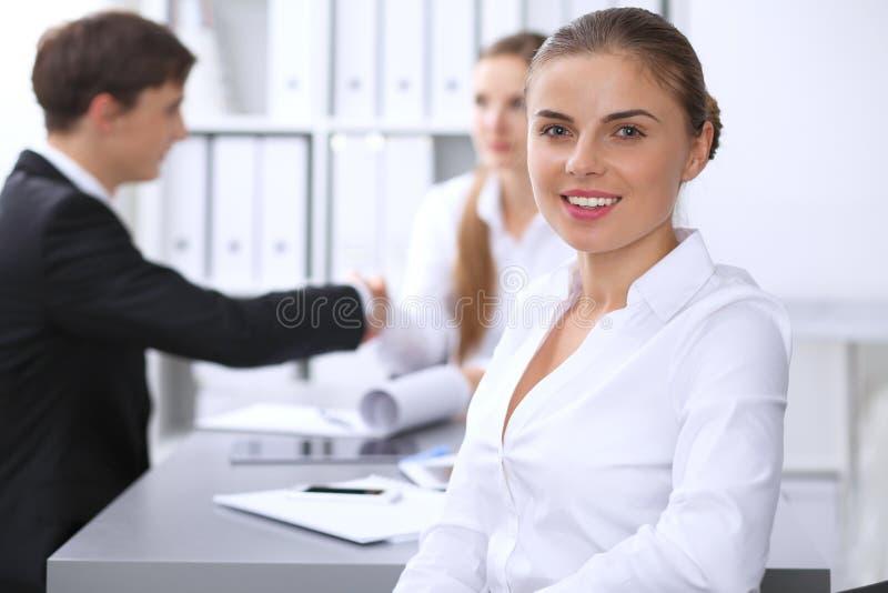 小组商人在关于办公室背景的会议上  在一名美丽的深色的妇女的焦点 免版税库存图片