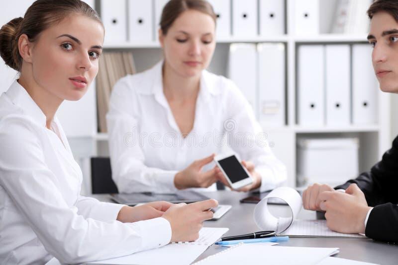 小组商人在关于办公室背景的会议上  在一名美丽的深色的妇女的焦点 库存图片
