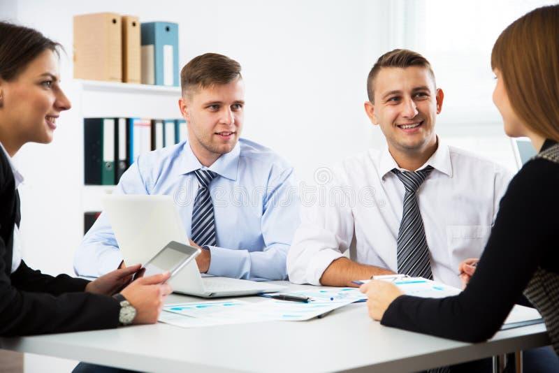 小组商人在桌附近的一次会议上 免版税库存照片