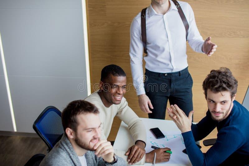 小组商人在现代会议室谈论工作结果 免版税库存图片