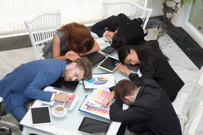 小组商人睡觉休息在会议室 库存图片
