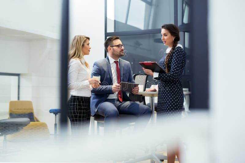 小组商人谈论关于项目的最新的细节在办公室 库存图片