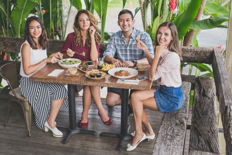 小组四最好的朋友吃午餐一起在咖啡馆 图库摄影