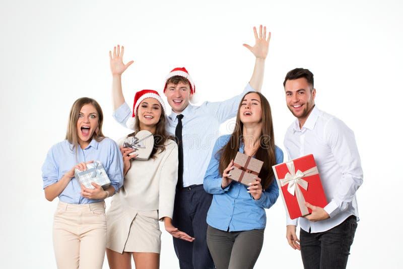小组圣诞老人帽子的年轻人有礼物盒的在他们的手上在白色 库存照片