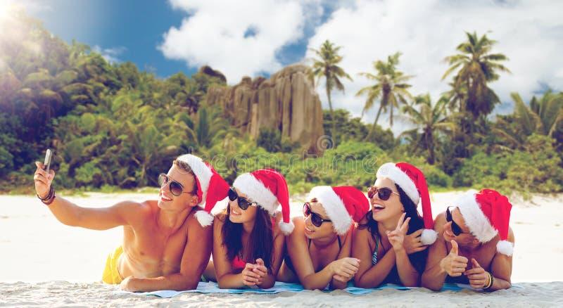 小组圣诞老人帽子的朋友有采取的selfie 免版税库存照片