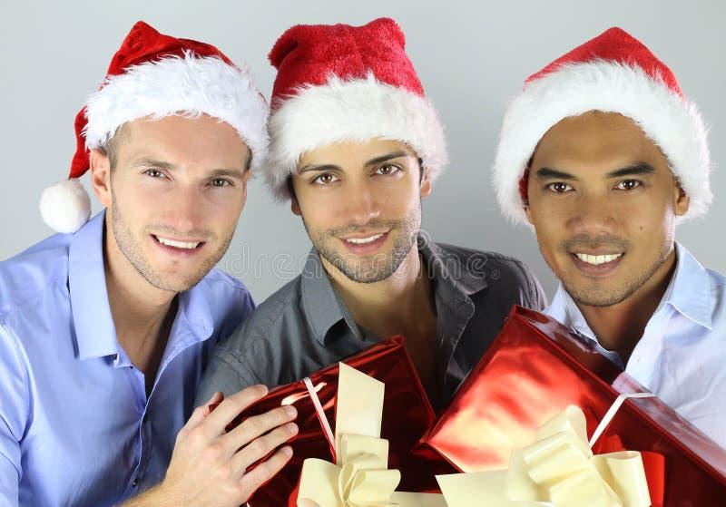 小组圣诞节帽子庆祝的愉快的快乐的多种族朋友 免版税库存图片