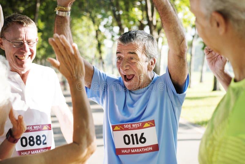 小组在公园的快乐的资深赛跑者 免版税库存图片