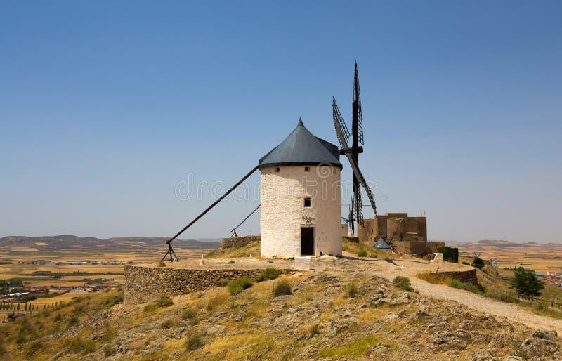 小组在坎波德克里普塔纳和卡斯蒂略de la穆埃拉的风车在背景 拉曼查,孔苏埃格拉,唐吉诃德路线,西班牙 库存照片