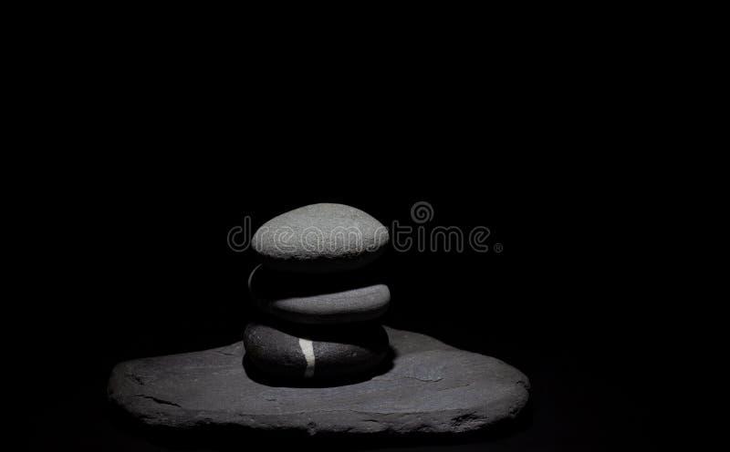 小组在柔光下的保持平衡的石头在黑背景 免版税库存图片