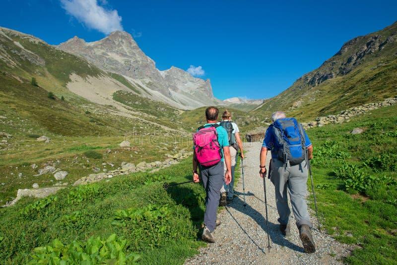 小组在步行期间的退休的年长远足者在山 库存图片