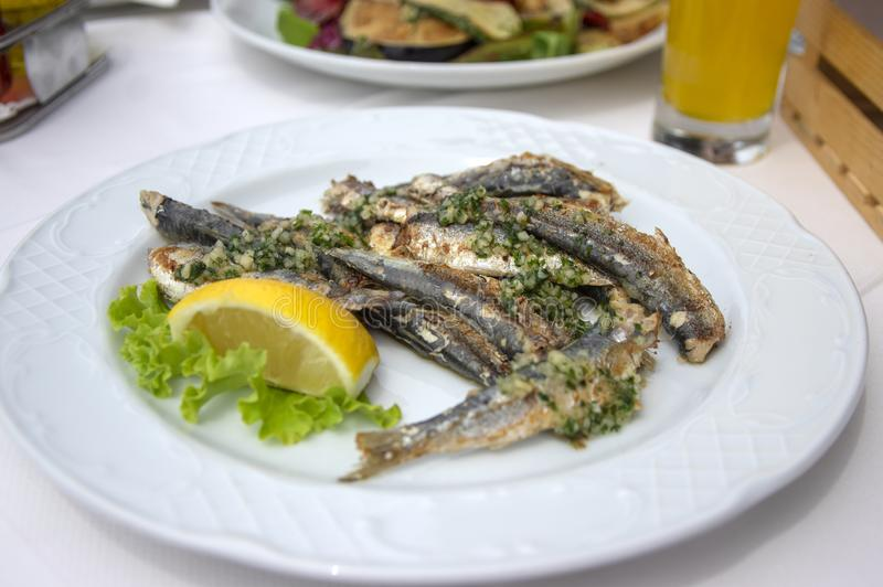 小组在白色板材的烤鲥鱼用黄色新鲜的柠檬和蔬菜沙拉,可口海鲜 库存图片