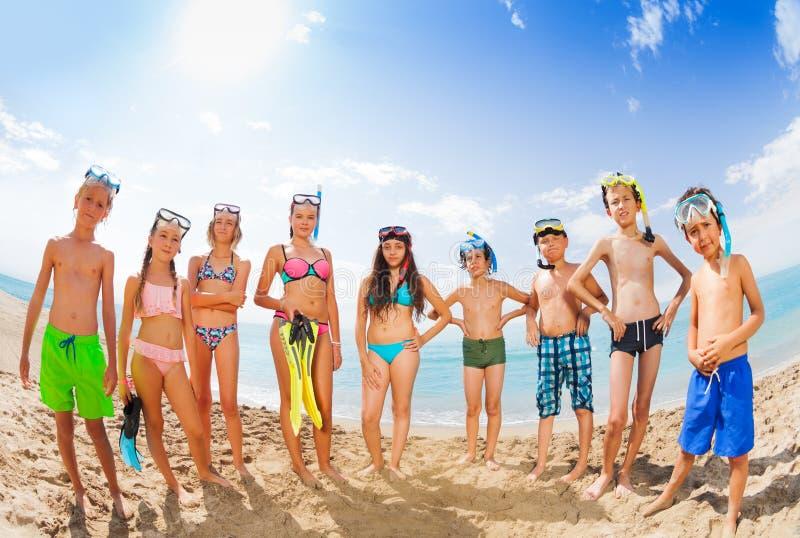 小组在站立在沙滩的泳装的孩子 免版税库存图片