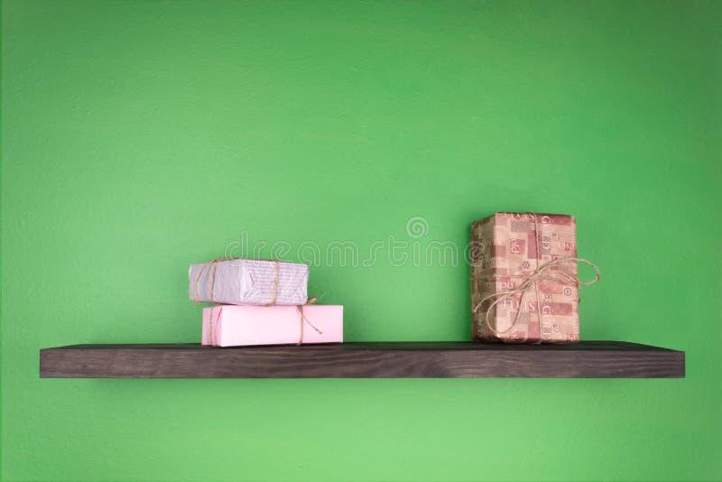 小组在绿色墙壁上被固定深色的架子的新年的礼物 免版税图库摄影