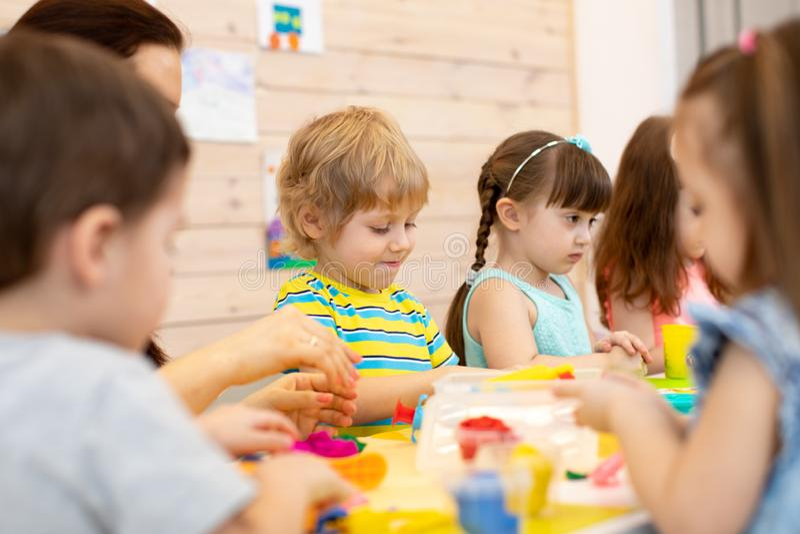 小组在艺术课的孩子与老师在幼儿园 库存照片