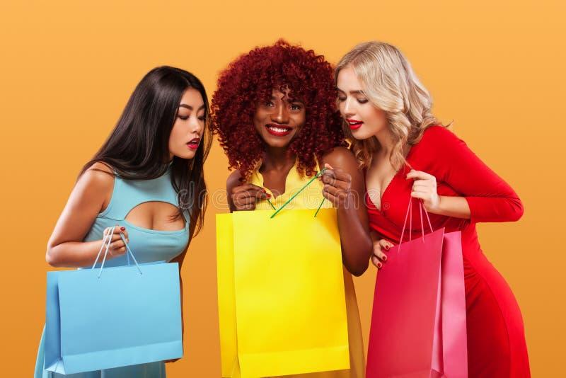 小组在购物以后的惊奇的妇女 美国黑人,亚洲和白种人种族 在黑星期五,橙色背景 免版税库存照片
