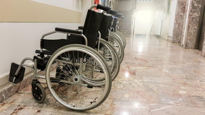 小组在走廊的空的轮椅准备好患者 免版税库存图片