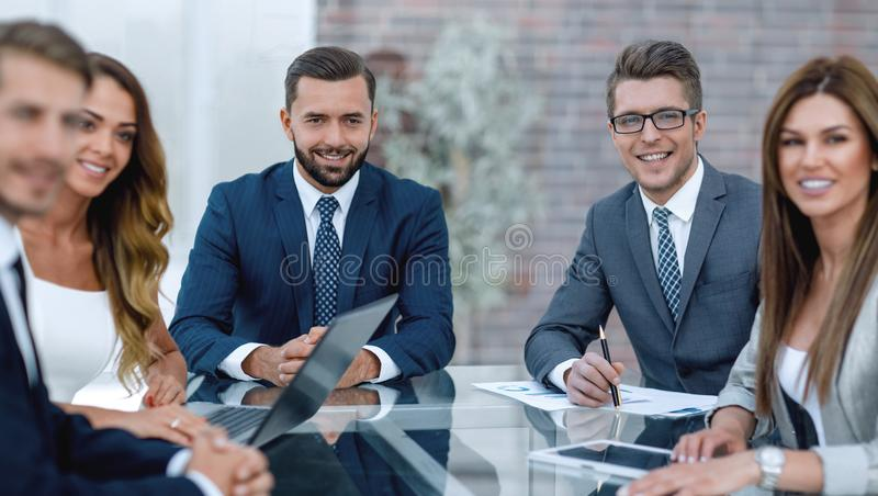 小组坐在书桌的商人 免版税图库摄影