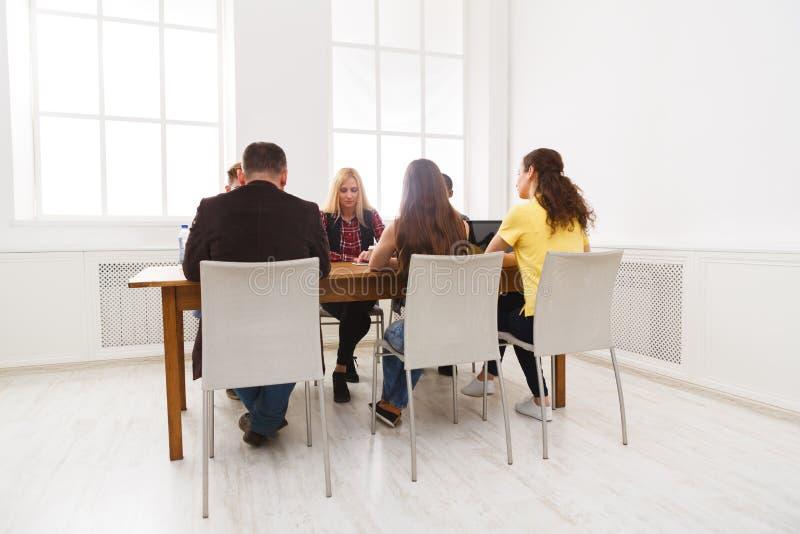 小组坐在办公室的商人 免版税库存图片