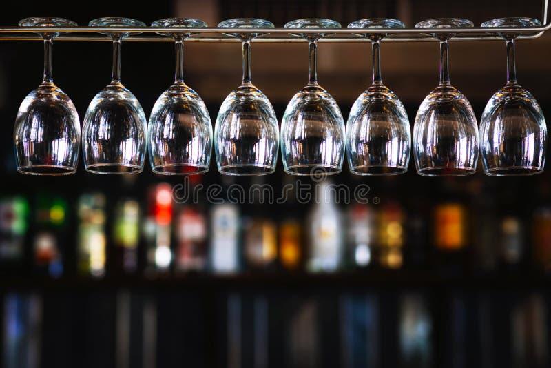小组垂悬在客栈& restaura的一个酒吧机架上的酒杯 免版税库存图片