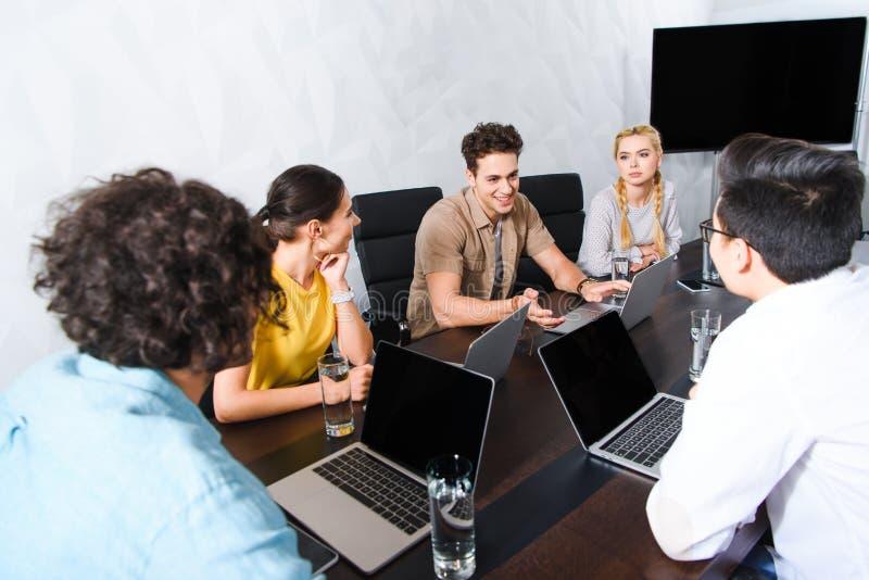 小组多文化商人有讨论在与膝上型计算机的桌上在现代 库存图片