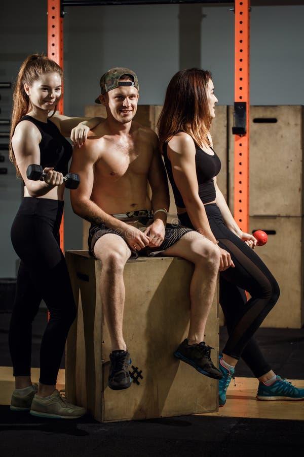 小组女性和男性成人一起坐箱子作为健身房的好朋友 图库摄影