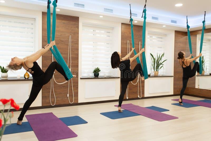 小组妇女做飞行在健身房的瑜伽伸展运动 适合和健康生活方式 免版税库存照片