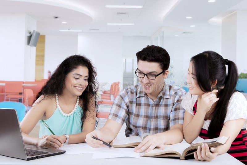 小组学习在图书馆里的大学生 免版税图库摄影