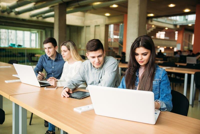 小组学习在学校图书馆里的大学生,女孩和男孩使用一台膝上型计算机并且连接到互联网 免版税库存图片