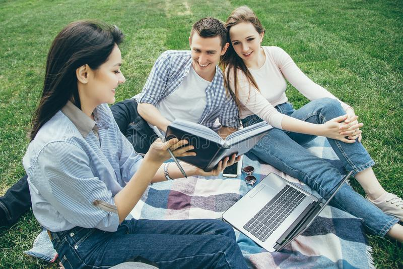 小组学生为研讨会做准备坐草坪 免版税库存图片