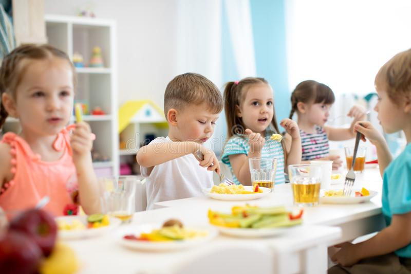 小组学龄前孩子吃午餐在托儿 吃健康食品的孩子在幼儿园 免版税库存照片