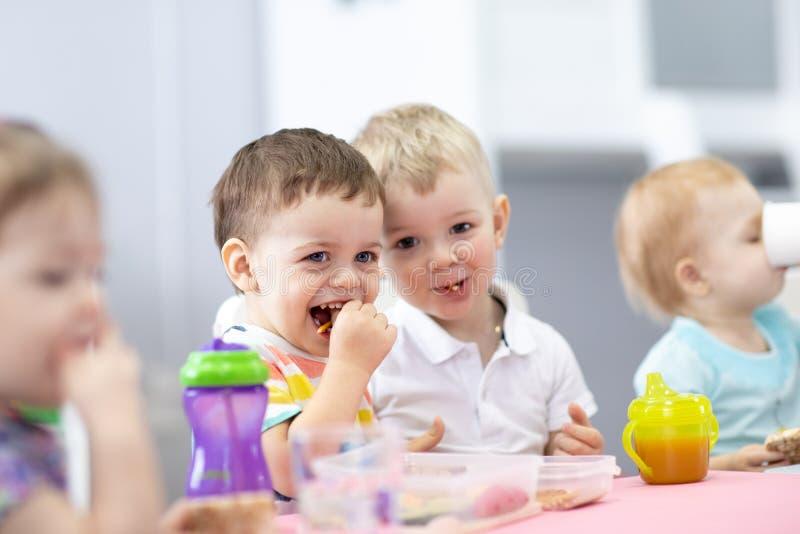 小组孩子吃午餐在幼儿园 免版税图库摄影