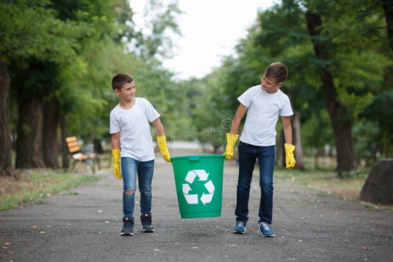 小组孩子志愿者帮助无用单元收集慈善环境,有选择性的软的焦点 小组工作 免版税库存照片