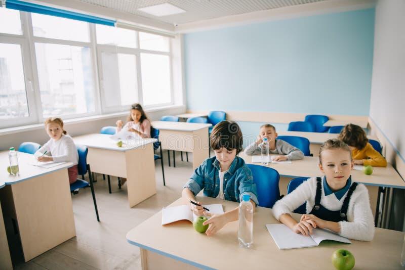 小组孩子用苹果和水坐 免版税图库摄影