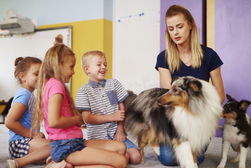 小组孩子获得与狗的乐趣在疗法期间 免版税图库摄影