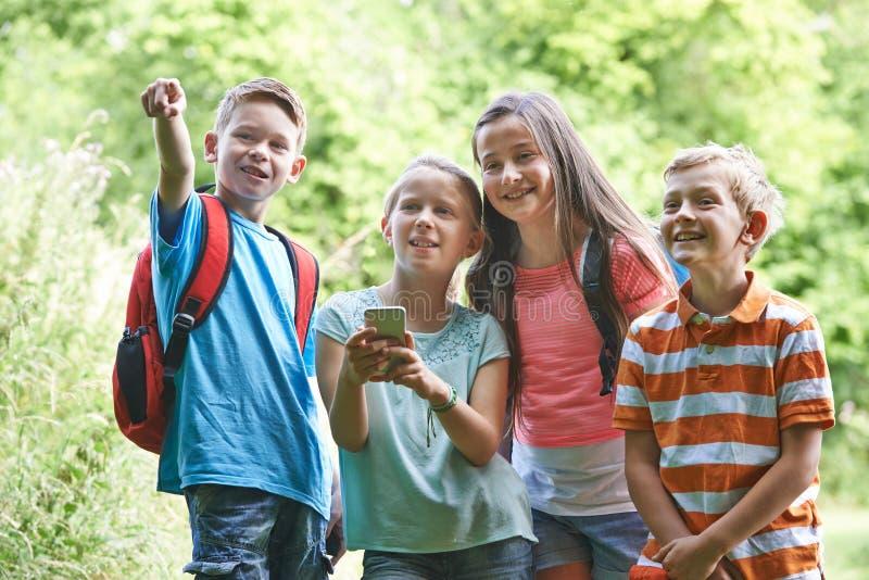 小组孩子Geocaching在森林 免版税库存图片