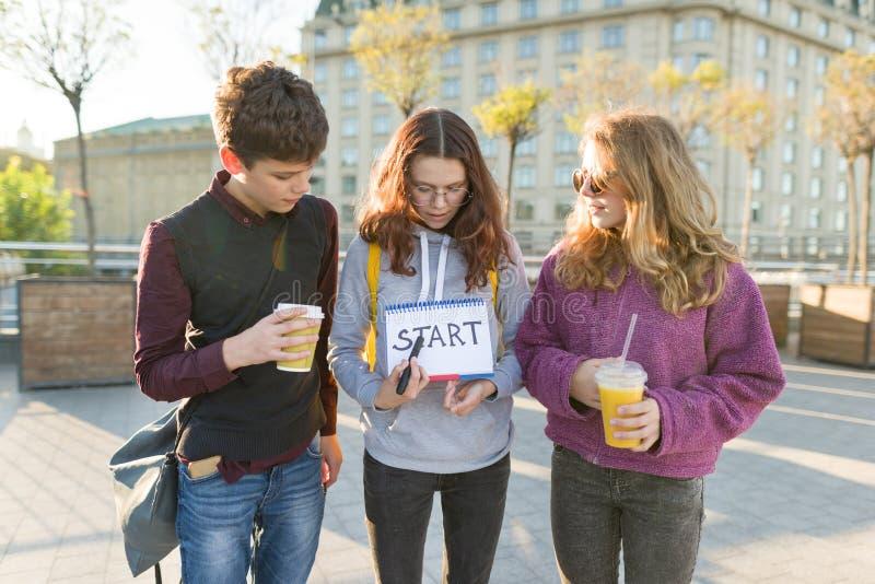 小组少年男孩和两个女孩,有一个笔记薄的与手写的词开始 库存图片