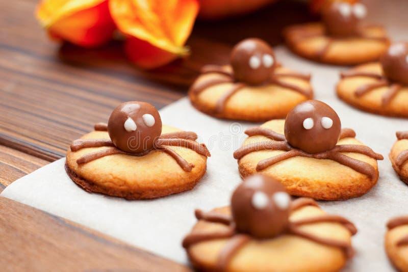 小组巧克力万圣夜在纸的蜘蛛曲奇饼为烘烤和木背景 库存照片