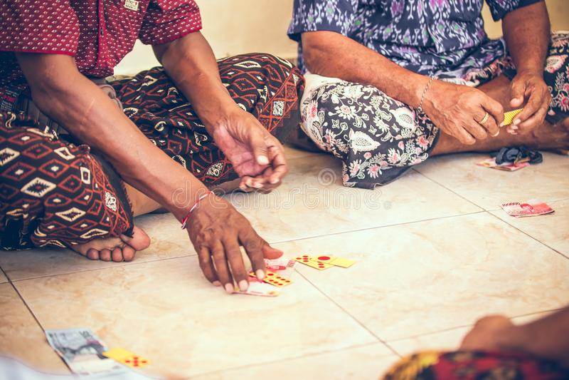 小组巴厘语人纸牌坐地板 巴厘岛 免版税库存照片