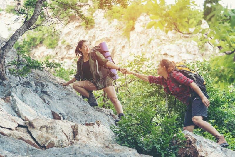 小组帮助她的朋友的远足者妇女爬上日落的最后部分在山的 走在室外lifest的旅客配合 免版税库存图片